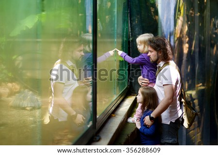 Father and his two little daughters looking at turtles though a glass at zoo - stock photo