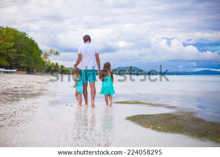 Father and his two little daughters walking by the sea - stock photo