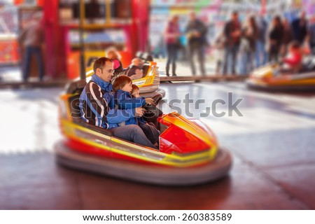 Father and his two sons,l having a ride in the bumper car at the amusement park - stock photo