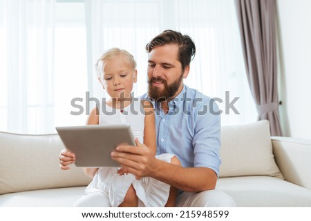 Father and his young daughter using digital tablet at home - stock photo