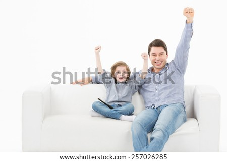 Father and his young son smiling on a couch white background - stock photo