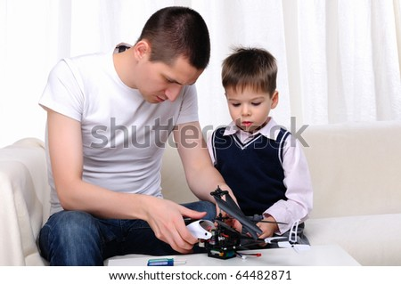 Father and his young son together renovating a small helicopter