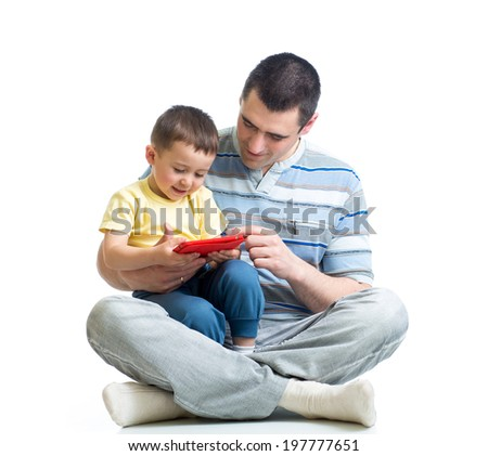 father and kid are looking to play and read tablet computer - stock photo