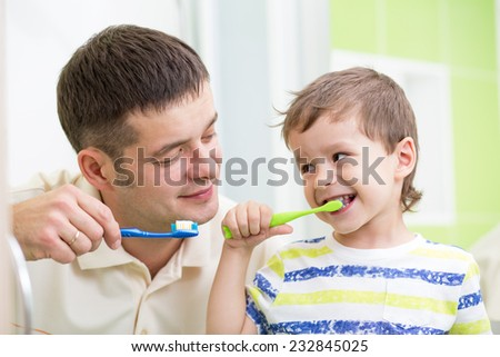 father and kid brushing teeth in bathroom - stock photo