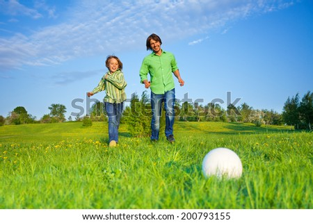 Father and kid playing football in park - stock photo