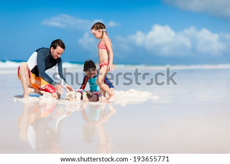 Father and kids enjoying summer beach vacation - stock photo