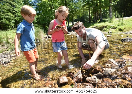 Father and kids in river building a dam with pebbles