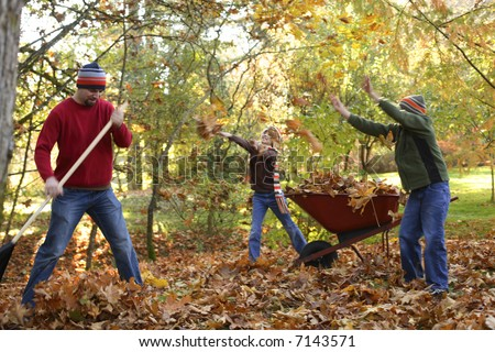 Father and kids playing in fall leaves - stock photo