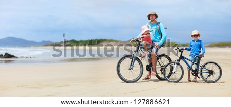 Father and kids riding bikes along a beach - stock photo