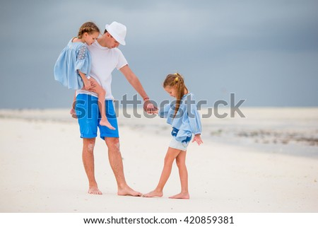 Father and kids walking on white sandy beach - stock photo