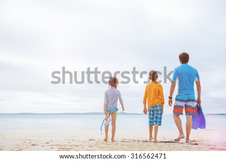 Father and kids with snorkeling equipment enjoying beach vacation - stock photo