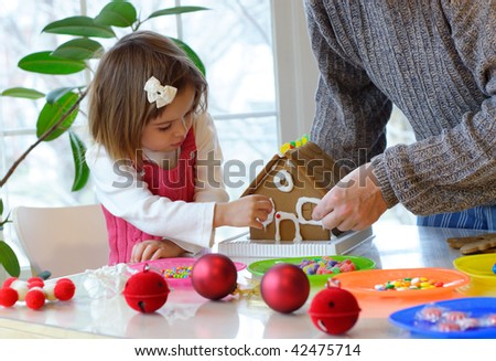 Father and little daughter assembling a gingerbread house - stock photo
