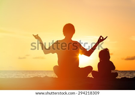 father and little daughter doing yoga at sunset beach