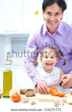 father and little daughter eating vegetables saladr in kitchen - stock photo