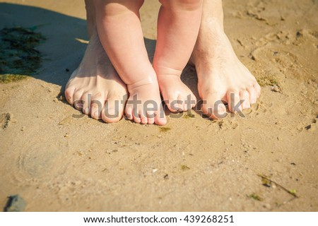 Father and little daughter feet at the beach on sand. Baby and father's feet. Summer beach background.