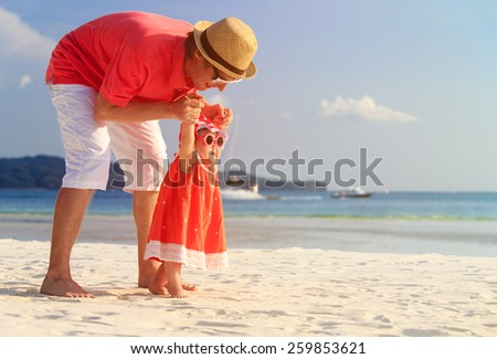 father and little daughter having fun on summer beach