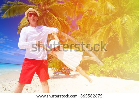 father and little daughter having fun on summer beach - stock photo