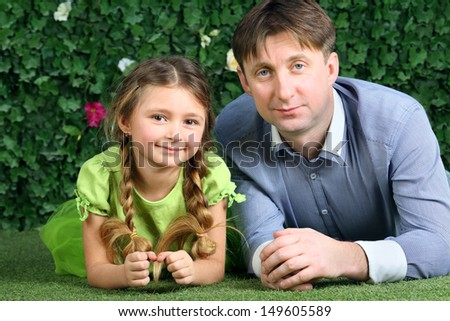 Father and little daughter lie on green grass near hedge in garden. - stock photo