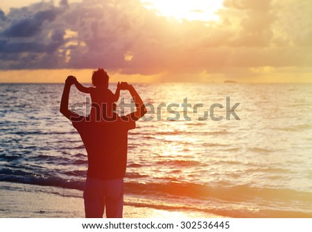 father and little daughter on shoulders having fun on sunset sky - stock photo