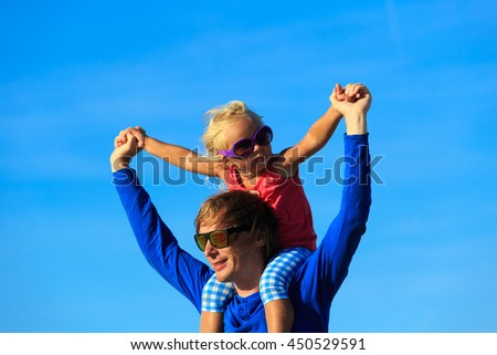 father and little daughter play at sky