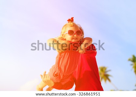 father and little daughter play at tropical beach - stock photo