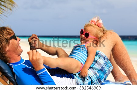 father and little daughter play on beach - stock photo