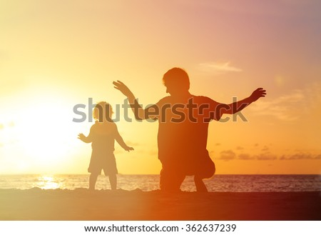 Father and little daughter playing silhouettes at sunset