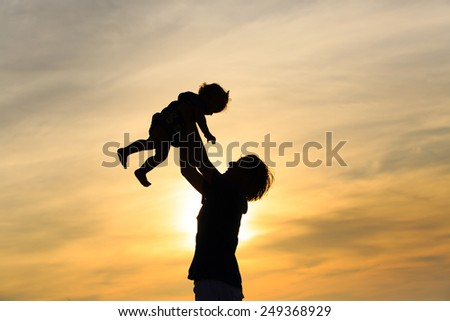 Father and little daughter silhouettes at sunset - stock photo