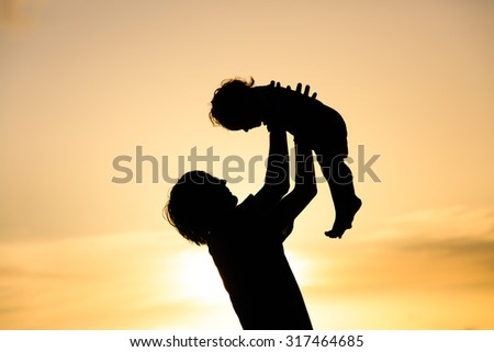 Father and little daughter silhouettes play at sunset - stock photo