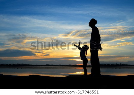 Father and little daughter silhouettes,They having fun on sunset beach