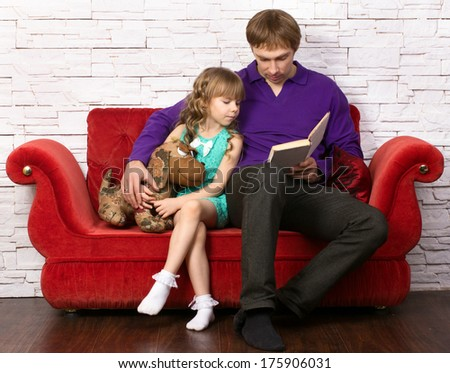 father and little daughter sitting on red sofa on modern background and reading book  - stock photo