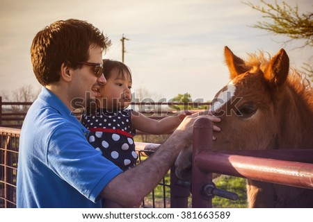 Father and little daughter touching new born horse with sweet vintage background color. filtered tone - stock photo