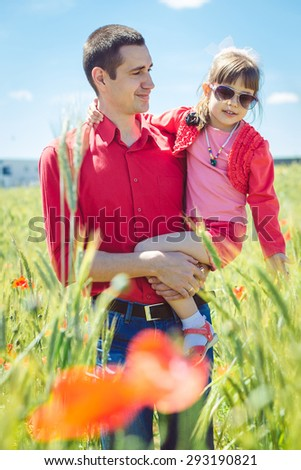 father and little daughter travel on summer wheat field