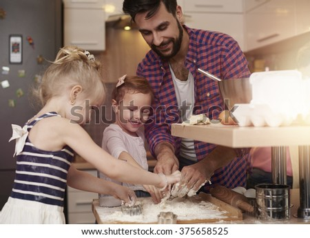 Father and little daughters having fun in the kitchen  - stock photo