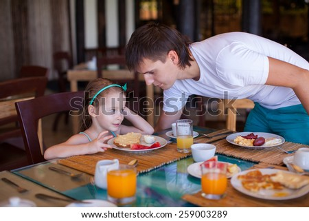 Father and little girl have breakfast together in outdoor cafe
