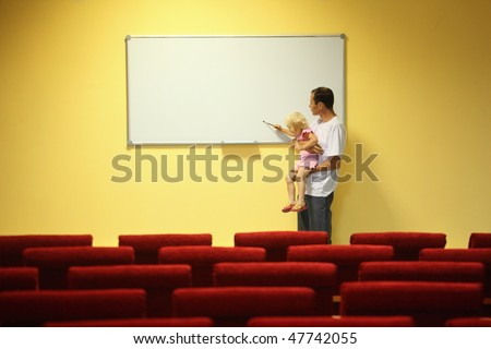father and little girl in empty presentation hall. little girl is drawing on a board - stock photo