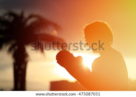 Father and little newborn daughter silhouettes at sunset