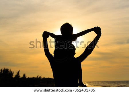 father and little son having fun at sunset - stock photo