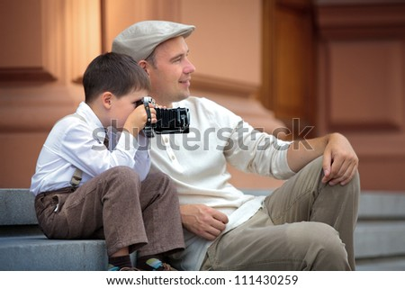 Father and little son holding retro camera in city - stock photo
