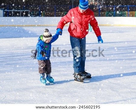 father and little son learning to skate in winter snow - stock photo