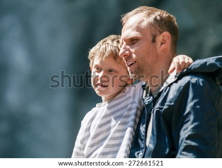 Father and little son outdoor portrait with waterfall background - stock photo