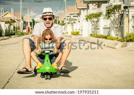 father and little son playing near a house at the day time - stock photo