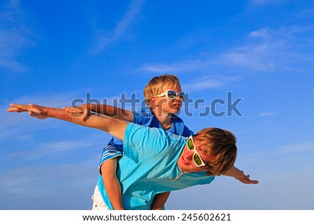 Father and little son playing on blue summer sky