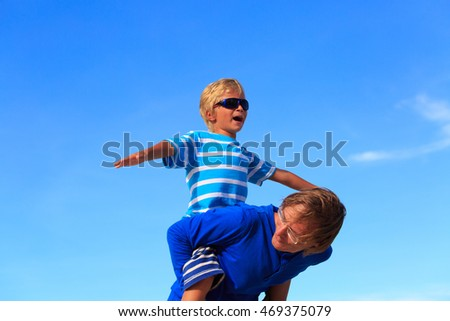 Father and little son playing on summer sky