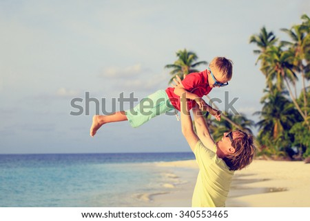 father and little son playing on summer tropical beach - stock photo