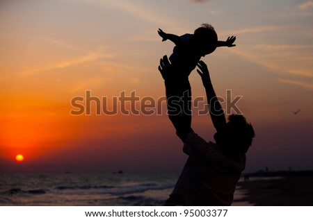 Father and little son silhouettes on beach at sunset - stock photo