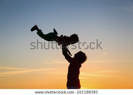 father and little son silhouettes play at sunset sky - stock photo