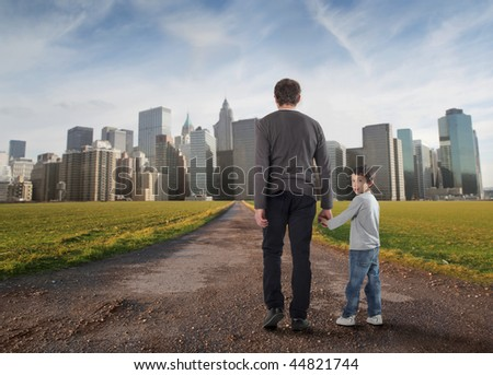 father and little son walking on a country road towards a modern city