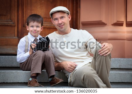 Father and little son with retro camera outdoors - stock photo
