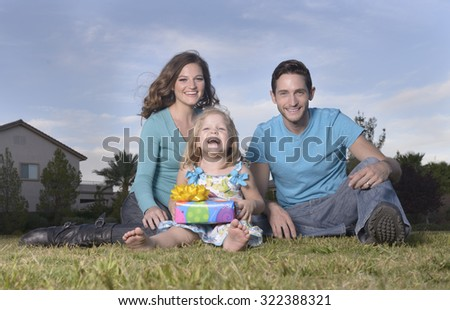 father and mother and daughter sitting on grass, dauther with wrapped present